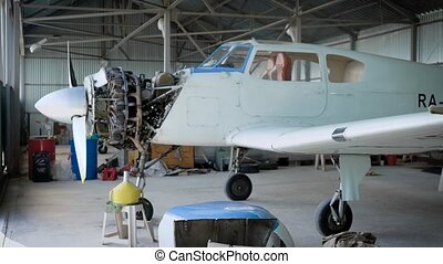Plane standing in aircraft hangar, plane engine, repairing the plane.