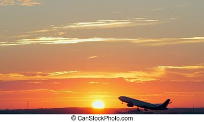 Plane taking off at golden sunset - Golden evening sky with...