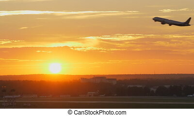 Plane taking off at sunset - Aerial shot of a jet plane...