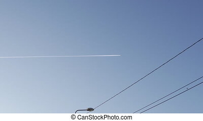 Plane trail at a clear sky high far away in the background