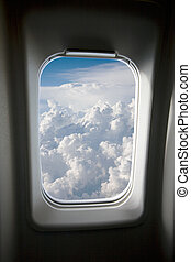 Plane Window - A view of clouds from an airplane window.