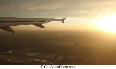 Plane Wing at Sunset - Looking out the window at the wing of...