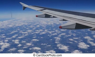 Plane wing over clouds and blue sky
