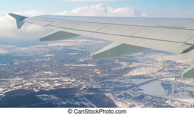 Plane wing through window with sky and city behind. Aircraft turn at flight