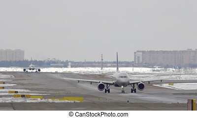 Planes taxiing on the snowy runway