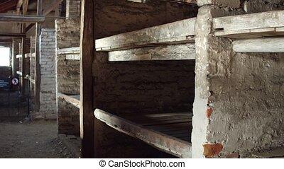 Plank beds in a concentration camp. 4K steadicam shot