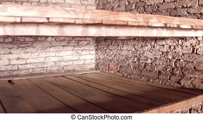 Plank beds in a concentration camp. 4K steadicam video