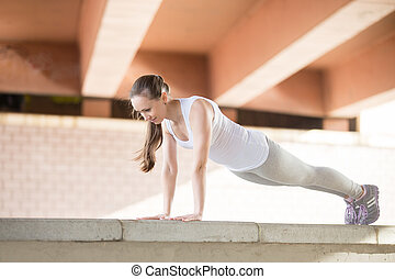 Plank yoga pose - Sporty young girl practicing yoga,...