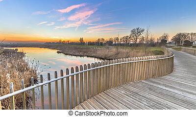 Plankied balustrade sunset over swamp