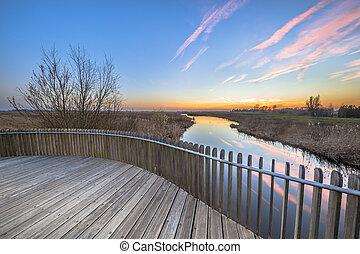 Planking balustrade sunset over swamp