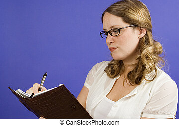 Planner - Young woman on blue writing in day planner