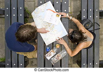 Planning a trip - Young couple planning a trip on a map,...