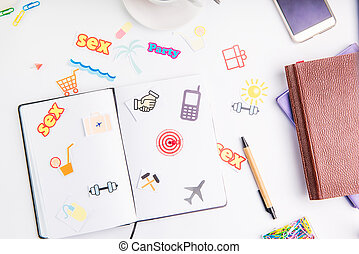 Planning Organizer with icons of actions and target with pushpin as an arrow on the working place with stationery and coffee. Creative concept of day planning and goals achievements in daily life.