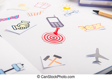 Planning Organizer with icons of actions and target with pushpin as an arrow on the working place with stationery. Creative concept of day planning, goals achievements in daily life. Selective focus.