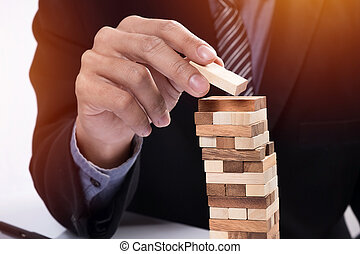 Planning, risk and strategy in business concept, businessman gambling placing wooden block on a tower