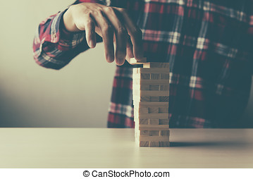 Planning, risk and strategy in business, man pushing wooden block