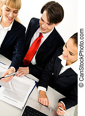 Planning - Group of three businesspeople sitting at the...