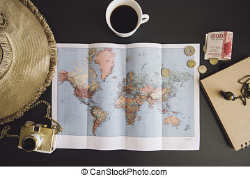 Planning the trip. World map with the hat, film camera, some money, notebook from recycled paper and freshly brewed coffee cup on the dark wooden table background.