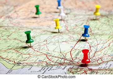 Several pushpins on a road-map of a tourist