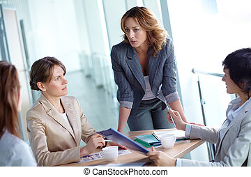 Planning work - Image of four businesswomen discussing...