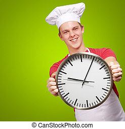 Plano de fondo, reloj, encima, joven, verde, tenencia, cocinero, retrato, hombre