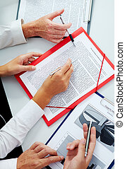 Plans - Three businesspeople presenting their papers and...