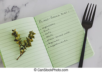 plant-based diet conceptual still-life, notebook with food category list with fork and small branch of leaves