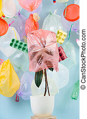 Plant in a pot covered with a plastic bag, against the background of garbage