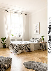 Plant next to bed in bright bedroom interior with poster and pouf next to fur. Real photo