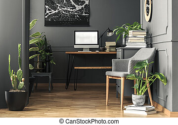 Plant next to grey armchair in home office interior with mockup of computer desktop. Real photo