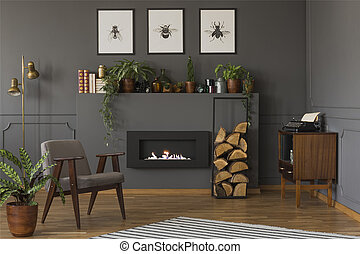 Plant next to grey armchair in warm apartment interior with...
