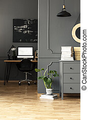 Plant next to grey cabinet in workspace interior with mockup of computer desktop. Real photo