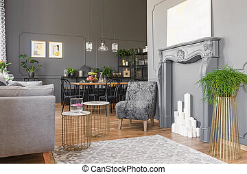 Plant on gold table and grey armchair in open space interior...