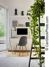 Plant on ladder in white home office interior with window and grey chair at desk with lamp. Real photo