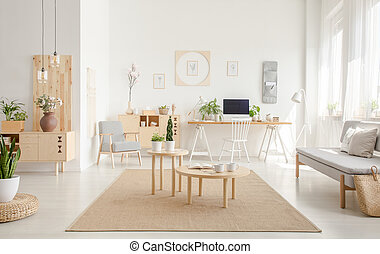 Plant on pouf neat wooden tables on brown carpet in spacious white flat interior with sofa. Real photo