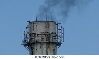 plant pipe smoke black against the blue sky environmental...