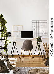 Plant, white lamp and desktop computer on desk in freelancer's interior with grey chair. Real photo