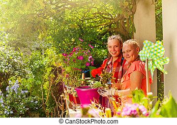 plantande, tonårs- flickor, två, utomhus, blomningen, lycklig