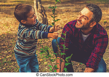 Planting a family tree. Happy young man planting a tree while his little son helping him