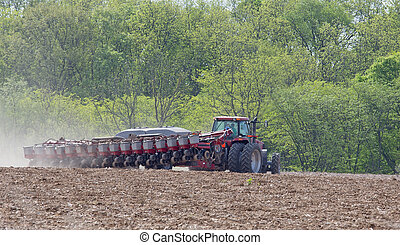 Planting a Farm Field - Farm tractor planting seeds in a...