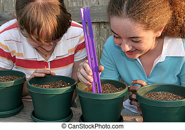 Planting Together - Two young girls working together on a...