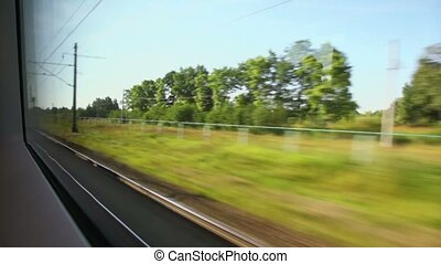 Plants and pillars with wires pass by during train trip at summer day