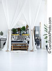 Plants in bright bedroom interior
