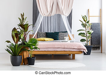 Plants in pastel bedroom interior