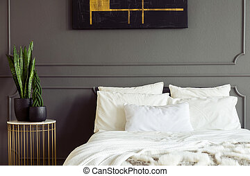 Plants on gold table next to white bed against grey wall with molding in bedroom interior. Real photo