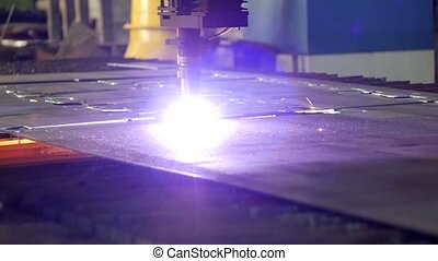 Plasma cutting of metal on an automatic laser machine, laser plasma cutting machine for cutting parts from metal, production, close-up