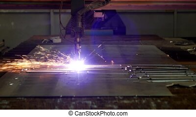 Plasma cutting of metal on an automatic laser machine, laser plasma cutting machine for cutting parts from metal, production, close-up, smoke