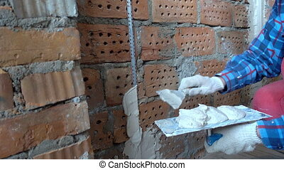 Plaster builder attach beacons to brick wall to apply plaster layer, Repair and construction, Shot in 4K UHD,