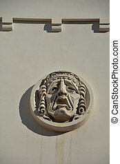 Plaster mask on wall of the theater