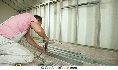 Plasterboard wall facing - A man using screwdriver to...